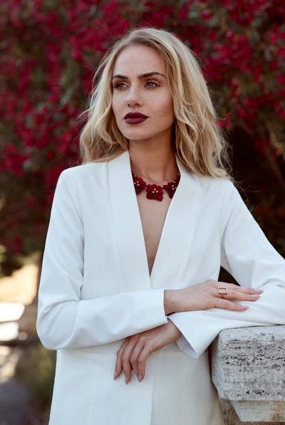 white jacket red necklace
